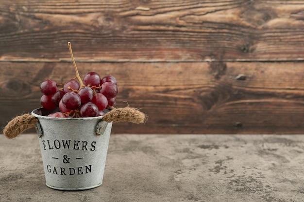 Cubo metálico de uvas rojas frescas sobre mesa de mármol.