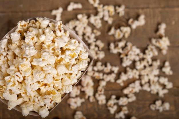 Cubo de palomitas de maíz para disfrutar de la película sobre fondo de madera. vista superior