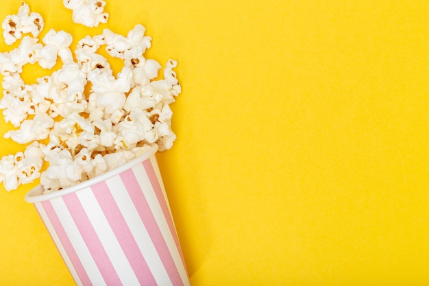 Cubo de palomitas de maíz sobre fondo amarillo. fondo de película o televisión. vista superior copia espacio