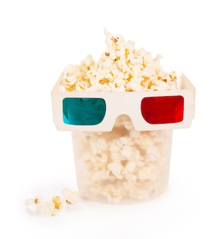 Cubo de papel rayado con palomitas de maíz y gafas 3d aislado sobre fondo blanco con trazado de recorte.