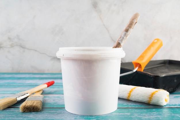 Cubo de pintura de primer plano con rodillos