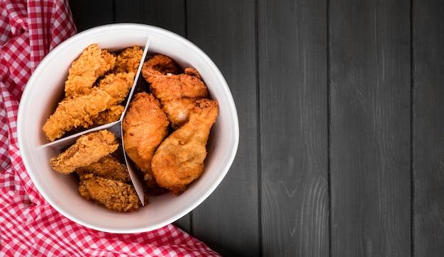 Cubo de pollo frito de vista superior con espacio de copia y toalla de cocina