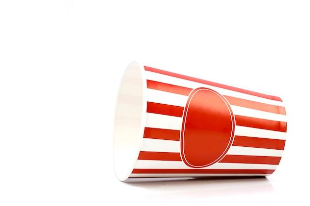 Cubo rayado rojo y blanco vacío para las palomitas de maíz aisladas en el fondo blanco