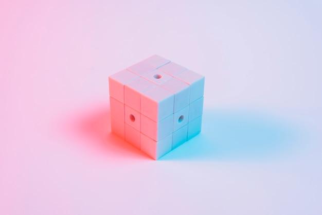 Cubo de rompecabezas pintado con luz azul y sombra sobre fondo rosa