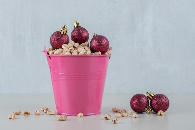 Un cubo rosa lleno de cereales saludables con bolas de navidad.
