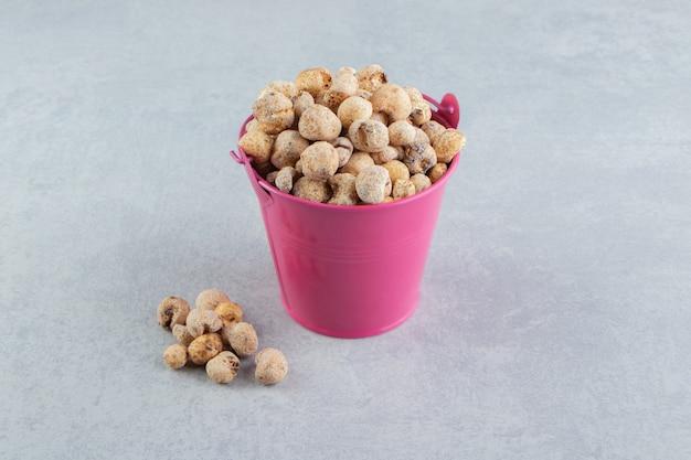 Un cubo rosa lleno de deliciosos frutos secos.