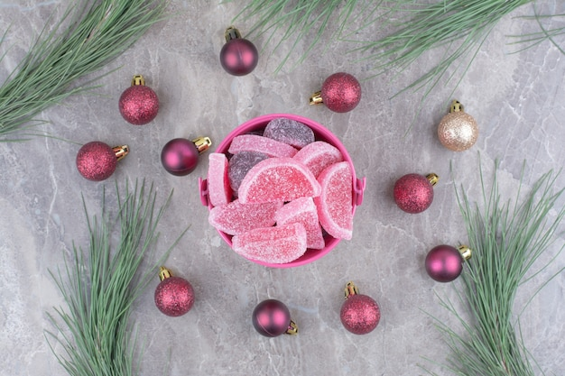Un cubo rosa lleno de mermeladas dulces con bolas rojas de navidad sobre fondo de mármol.