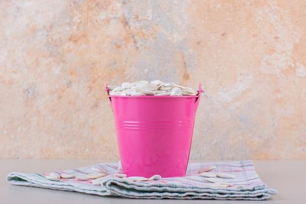 Cubo rosa lleno de semillas de calabaza orgánicas