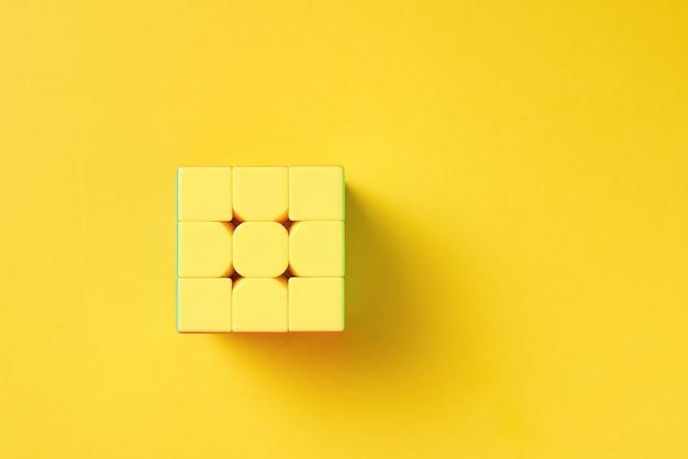 Cubo rubics sobre un fondo amarillo, vista desde arriba