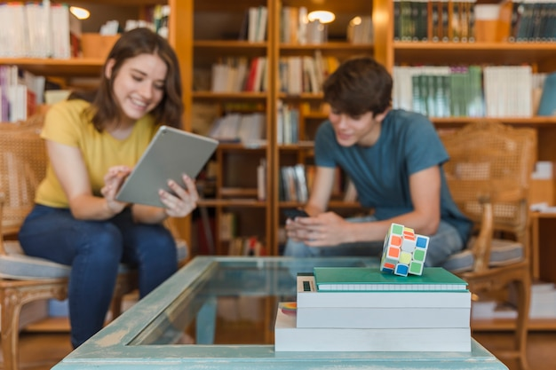 Cubo de rubik y libros de texto cerca de adolescentes que estudian