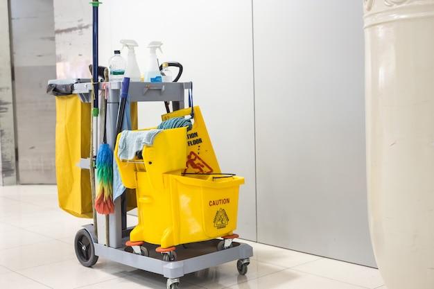 Cubo de trapeador amarillo y conjunto de equipos de limpieza en el aeropuerto