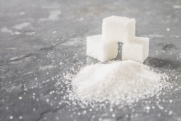 Cubos de azúcar y arena de azúcar sobre un fondo gris oscuro.