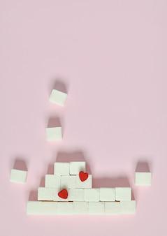 Cubos del azúcar blanco en un fondo rosado. ¿cuáles son los conceptos de diabetes y la ingesta de calorías?
