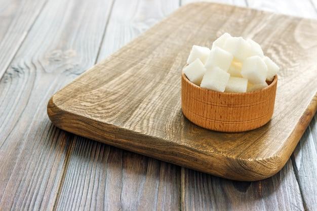 Cubos de azúcar blanco en un tazón. enfoque selectivo