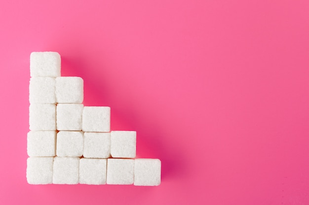 Cubos de azúcar sobre un fondo rosa.