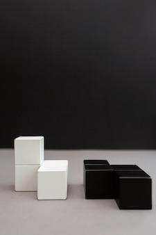 Cubos blancos y negros sobre un fondo gris-negro. rompecabezas de madera.