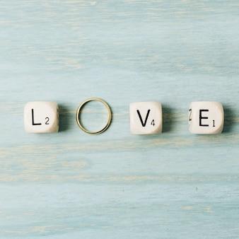 Cubos de la carta de amor con el anillo de bodas de oro sobre fondo de textura de madera
