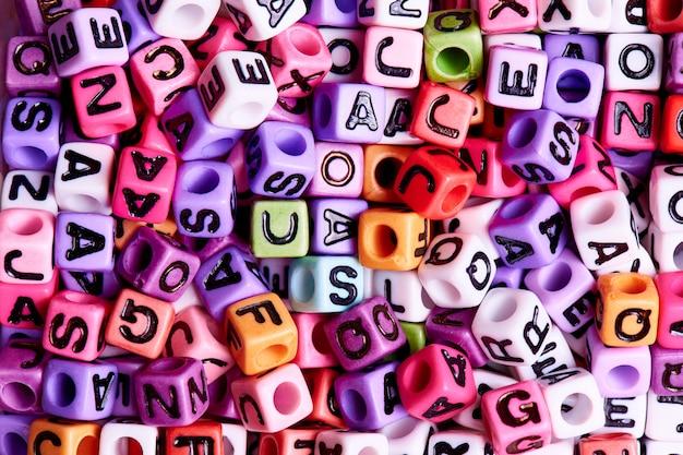 Los cubos coloreados con inglés ponen letras al primer. concepto de la textura y del fondo.