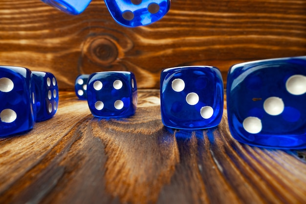Cubos de dados azules contra la superficie de madera marrón