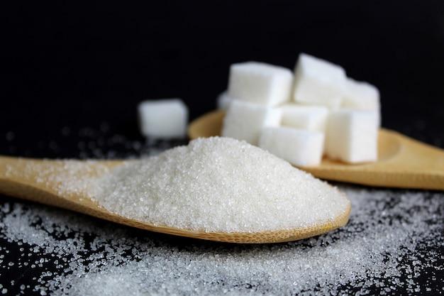 Cubos desmenuzables y de azúcar y refinados se encuentran en cucharas de madera sobre una pared negra. delicioso producto dulce y rico en calorías.