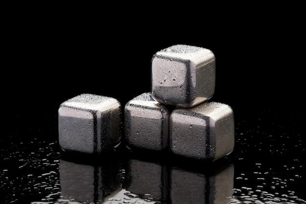 Cubos de enfriamiento de acero para cóctel sobre fondo de vidrio