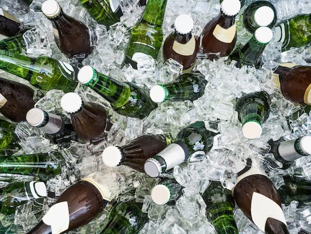 Cubos de hielo y botellas coloridas con cerveza fría.