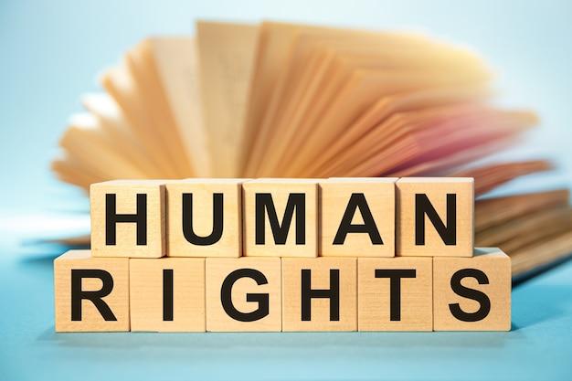 Cubos de madera con la abreviatura derechos humanos sobre un libro abierto.