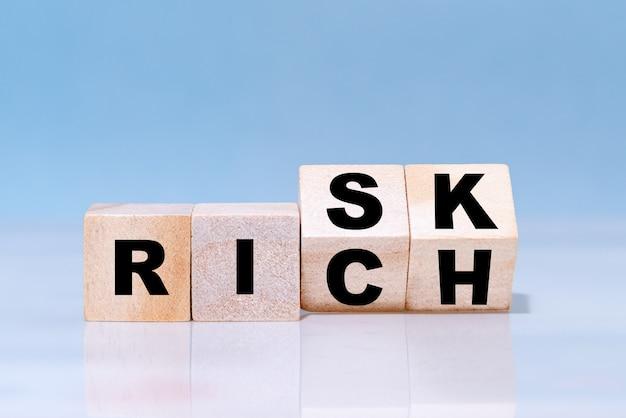 Los cubos de madera se dan la vuelta para cambiar el concepto de redacción riesgo o rico.