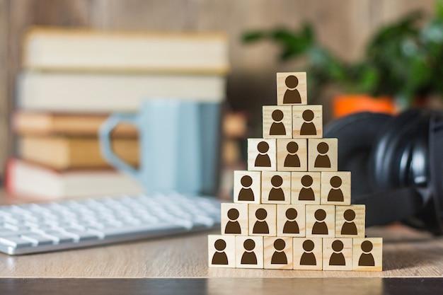 Cubos de madera con hombres alineados con una pirámide y escritorio de oficina con una computadora portátil, teclado, auriculares, taza. concepto de corporación, pirámide financiera, liderazgo, equipo unido