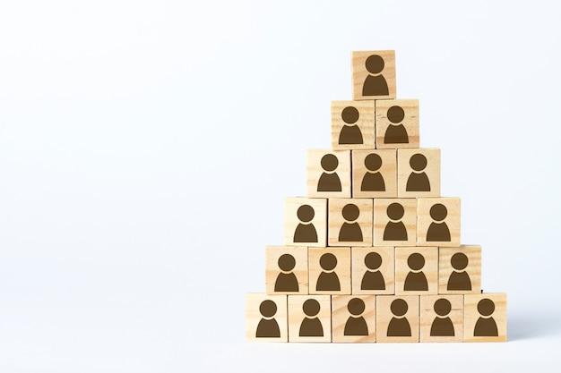 Cubos de madera con hombres alineados con una pirámide sobre un fondo blanco claro. concepto de corporación, pirámide financiera, liderazgo.