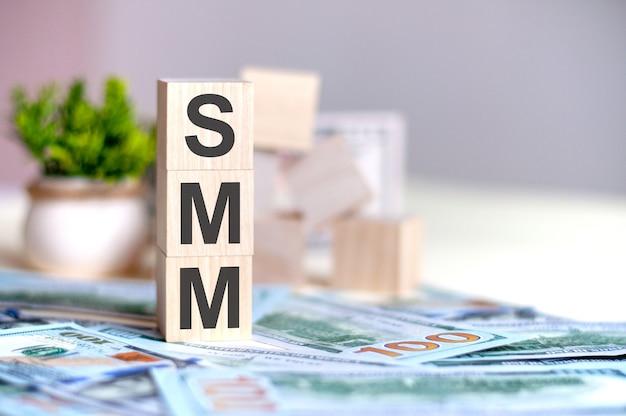 Cubos de madera con las letras smm dispuestas en una pirámide vertical sobre billetes, planta verde en una maceta en el fondo.