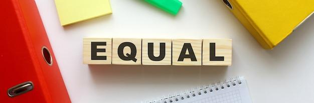 Cubos de madera con la palabra igual en el escritorio de oficina. carpeta y otros útiles de oficina.