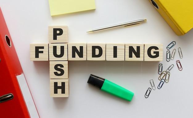 Cubos de madera con palabras push funding en el escritorio de la oficina.