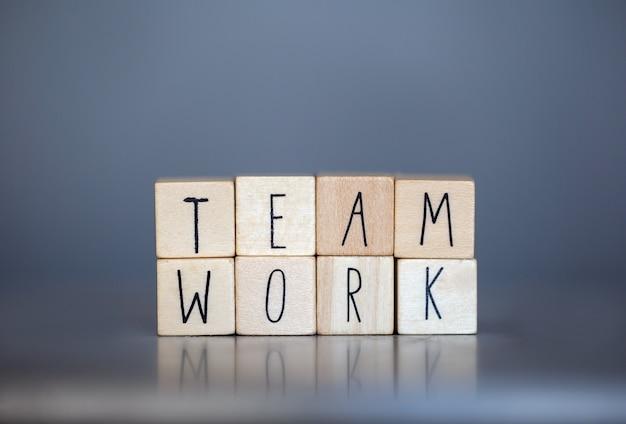 Cubos de madera con las palabras team work para el concepto de negocio en la pared azul gris, trabajando juntos