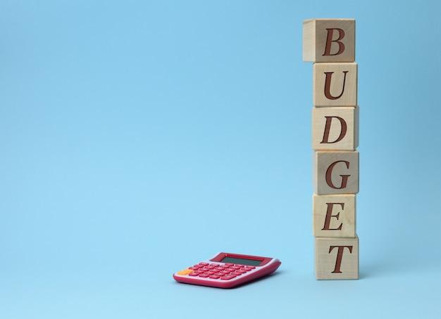 Cubos de madera con el presupuesto de inscripción y una calculadora rosa sobre una superficie azul