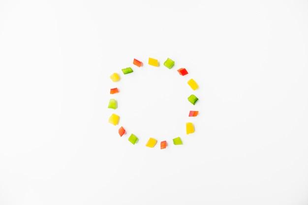 Cubos de pimientos coloridos formando marco sobre fondo blanco