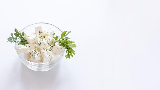 Cubos de queso blanco con perejil en el recipiente de vidrio sobre fondo blanco