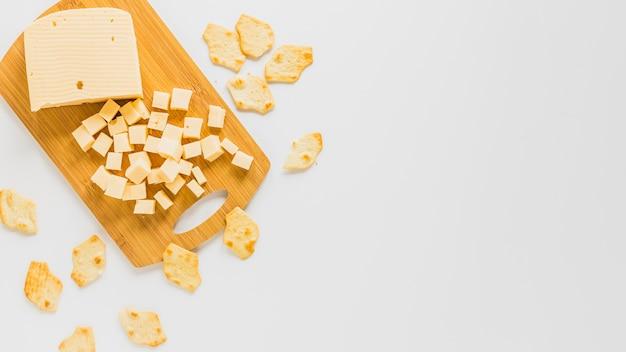 Cubos de queso y galletas aisladas sobre fondo blanco