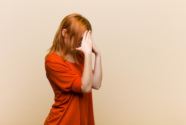 Cubriendo los ojos con las manos con una mirada triste y frustrada de desesperación, llanto, vista lateral