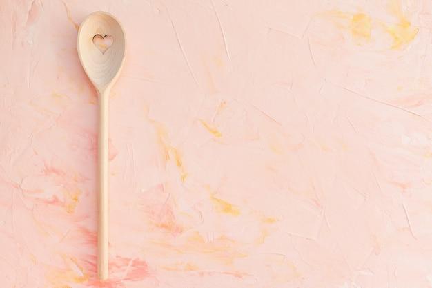 Cuchara agitadora con corazón sobre fondo rosa