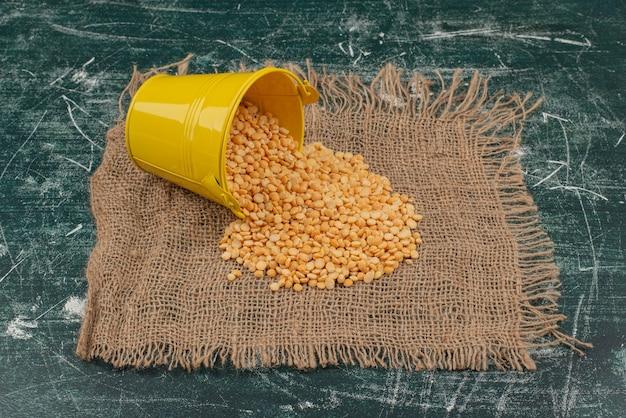 Cuchara amarilla con trigo sobre arpillera sobre mesa de mármol