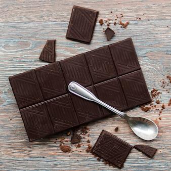 Cuchara y barra de chocolate negro.