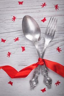 Cuchara y bifurcación del vintage con una burocracia, ángeles y mariposas para el día de tarjeta del día de san valentín en una tabla de madera.