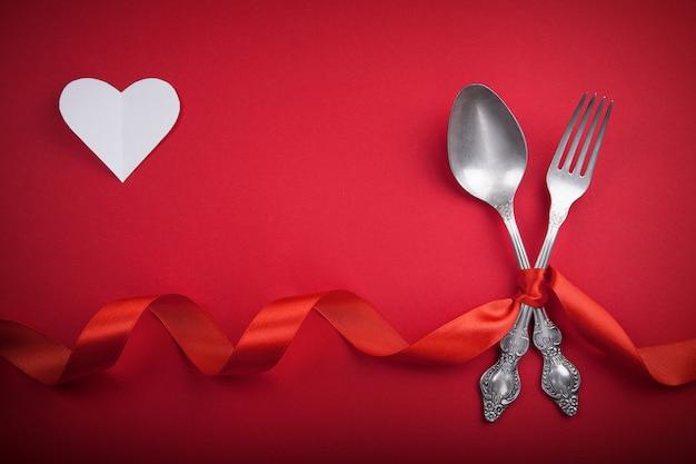 Cuchara y bifurcación del vintage con una cinta roja y un corazón blanco para el día de tarjeta del día de san valentín.