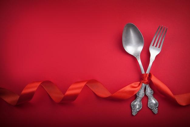 Cuchara y bifurcación del vintage con una cinta roja para el día de tarjeta del día de san valentín.