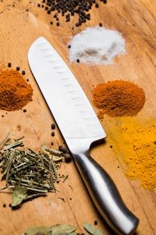Cuchara, cuchillo y montón de especias sobre la mesa