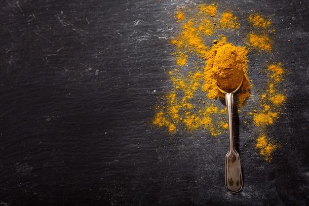 Cuchara con curry en polvo sobre fondo oscuro