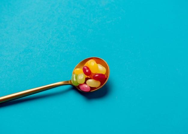 Cuchara dorada con caramelos en la pared azul
