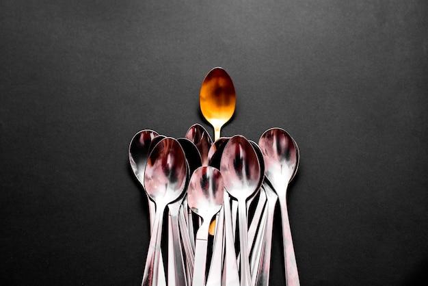 Una cuchara dorada de lujo se destaca del resto de cubiertos más sencillos y económicos, aislada sobre un fondo negro con espacio de copia.