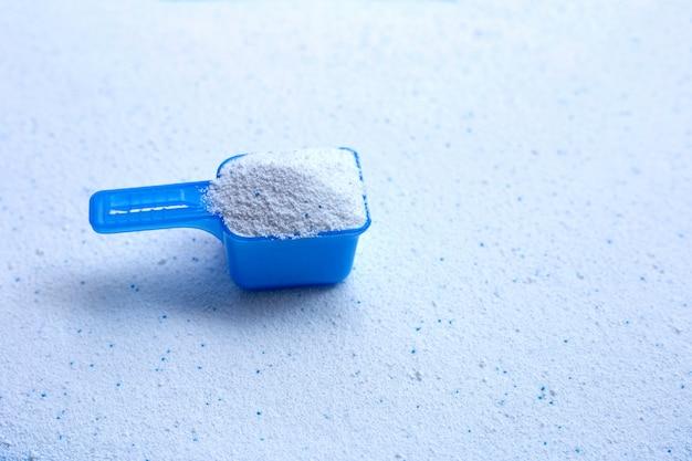 Cuchara dosificadora azul con detergente en polvo.